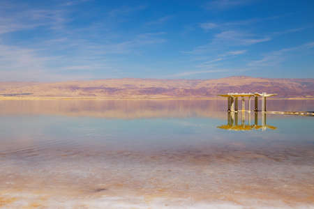 Beautiful view of salty Dead Sea shore with clear water and blue sky. Ein Bokek, Israel.