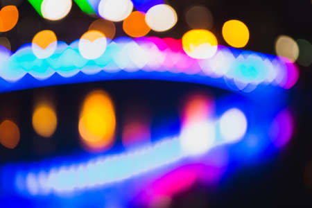 Abstract defocused background of colorful city lights at night. Blurry backdrop
