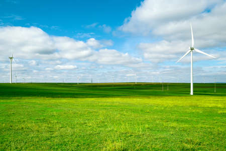 Wind turbines against beautiful blue sky with clouds. Eolic park. Eco farm of clean energy. Green ecological power energy generation concept.
