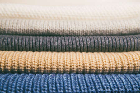 Stack of knitted  sweaters. Fall and winter season knitwear. Warm clothes concept.