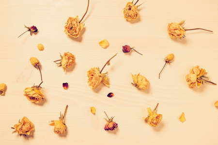 Flower composition made of dried rose buds on wooden background. Beautiful backdrop for blogs, seasonal cards and web design.Top view. Flat lay. Copy space