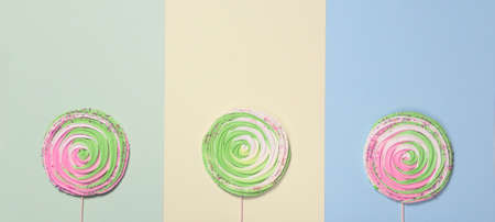 Colorful meringue on stick on colorful background. Festive and party concept. Minimal style. Flat lay. Top view