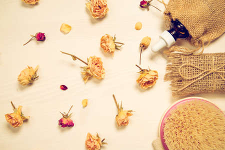 Set of natural soap, aroma oil, white towel and body brush with dried rose buds as a decoration on wooden background. Home spa concept. Beauty rituals theme. 版權商用圖片