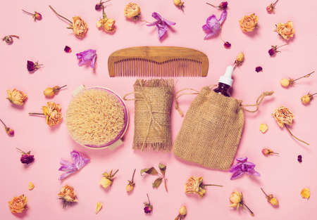 Set of natural soap, aroma oil, wooden comb  and body massage brush with dried rose and orchid buds as a decoration on pastel background. Home spa concept. Beauty rituals theme. 版權商用圖片