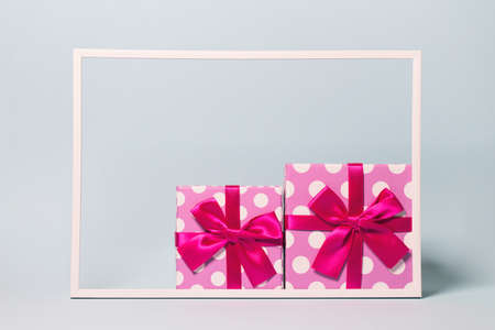 Two present boxes with dots  wrapped with bright ribbon on pastel background. Festive and holiday theme. Christmas or birthday gift. Sales and shopping concept.