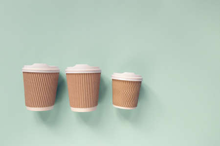 Paper cups of coffee to go on pastel background. Flat lay.