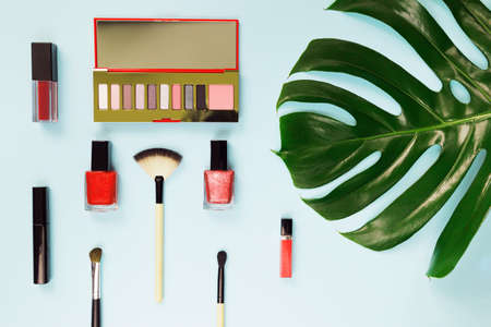 Set of decorative cosmetics with makeup brush  on colorful pastel background with monstera leaf. Top view
