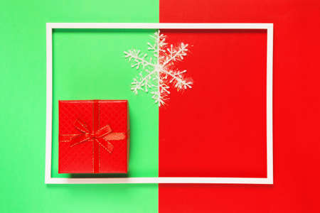 Chrismas composition with present box and decorative snowflake on red and green background with white frame. Winter holiday concept. Flat lay. Top view Stock Photo
