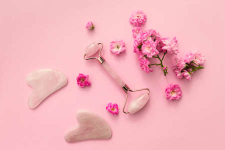 Facial massage kit for home spa. Face roller and gua sha massager made from rose quartz on pink pastel background with rose buds. Natural treatment concept. Stok Fotoğraf