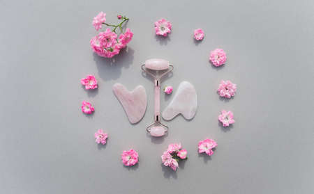 Facial massage kit for home spa. Face roller and gua sha massager made from rose quartz on pastel background with rose buds. Natural treatment concept.