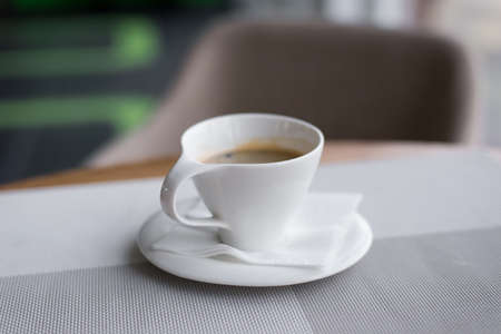 Cup of coffee on the table in an empty café closeup Stock Photo