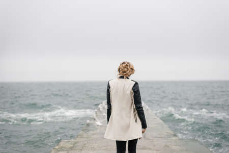 The beautiful girl stands with her back on the pier and looks at the sea.
