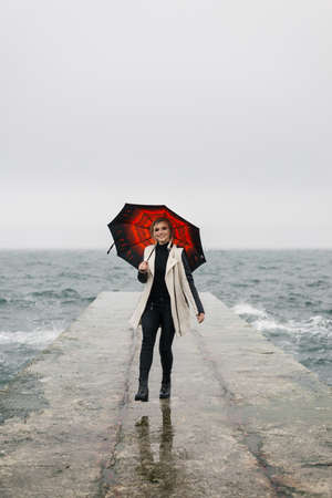 The girl steps into a jump on the pier, she cheerfully smiles and holds an umbrella in her right hand. Editorial