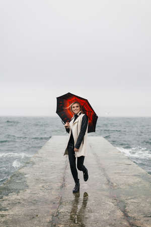 Smiling girl is standing on the pier holding an umbrella. It stands as if dancing on the spot. Editorial