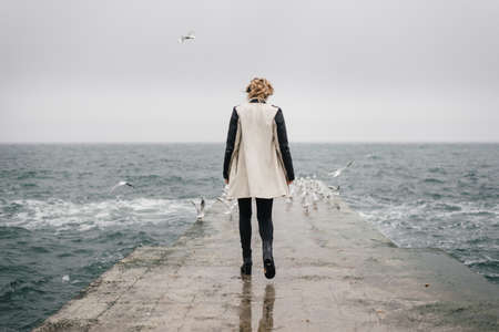 The girl is walking back on the pier and looking at the sea, and the seagulls, fleeing at the edge of the pier. She is careful walking on a wet surface of waves