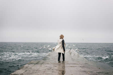 A pretty young student is walking back on a damp pier and looks at the waves. She is looking into the distance and the wind is waving er white cloak. Gulls gathered on the pier complement her romantic shape. Stock Photo