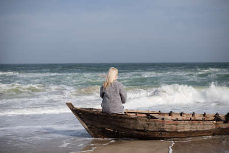 young slender girl sitting alone in a wooden boat by the sea and looking out into the distance