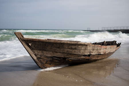 the sea during the storm covers the waves of an old small wooden boat on the shore
