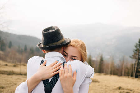 warm embrace between a man and a woman, gentle and a little timid