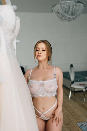 Portrait of a bride with a big bust in white lace underwear 免版税图像 - 107334576