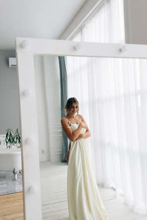 bride in lingerie and robe about to put on a wedding dress