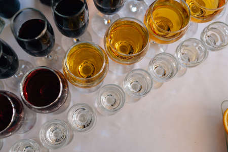 Glasses with alcohol stand in a row. Top view.