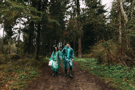 together overcome any difficulties. Bride and groom dressed in raincoats go through the swamp on their wedding day