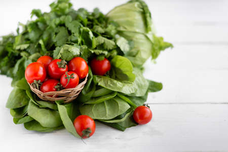 tasty vegetable food, red and juicy tomatoes near the leaves of green salad on a wooden table