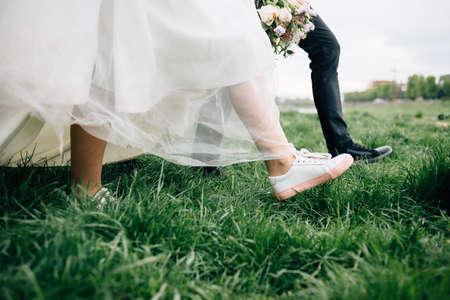 Close-up foto van de lopende benen van de bruid en bruidegom. pasgetrouwden in schoonheid in Stockfoto