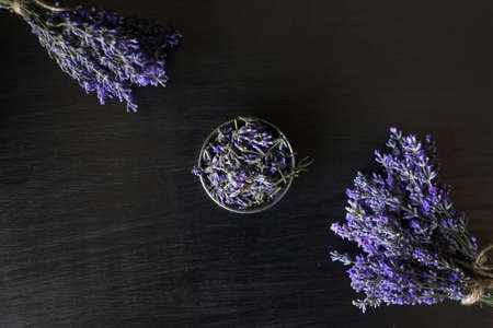 on a black background are bouquets of lavender scent and a bowl of fragrant flowers. natural cosmetics for the whole family. 免版税图像