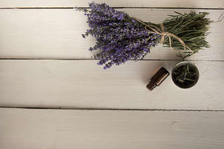a bouquet of fresh wildflowers of lavender next to it is a bottle of lavender oil and a stick on a white background.