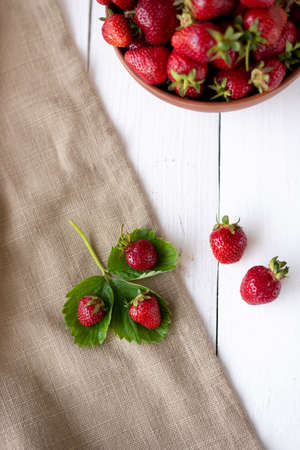 A pile of fresh strawberries in a bowl on a white wooden background. View from above. Agriculture