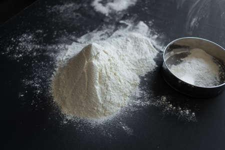 white wheat flour on the table, next to it lies a sieve. Bread making process Stockfoto