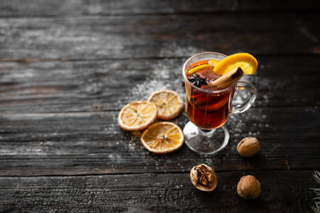 Christmas concept, a glass of tasty and fragrant mulled wine. Cinnamon stick and slices of dry orange lie on a wooden table