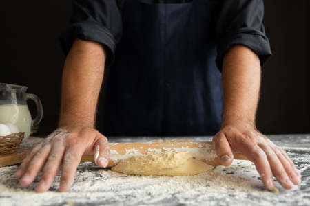 the process of rolling out the dough, male hands of the chef close-up, flour lies on the table. Chicken eggs and milk