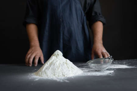 male hands the chef on the table, white wheat flour on the table. The process of cooking pasta. Ingredients in the kitchen Standard-Bild