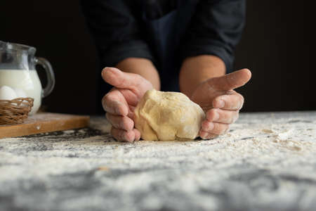 the ingredients for pizza are on the table, the chefs male hands knead the dough.