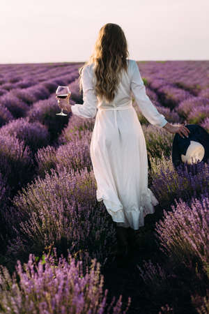 Picnic in nature, a young beautiful girl stands on a lavender field, a glass of wine, female hands