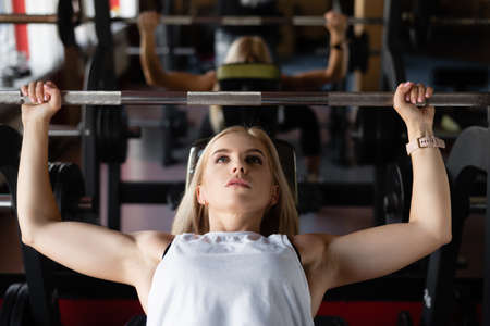 training in the gym, a young beautiful girl is engaged on a bench, doing bench press.