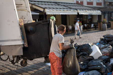 cleaning of household waste from the city streets, a man loads garbage bags into a garbage truck. Environmental pollution