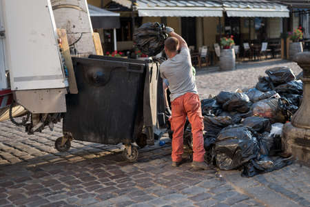 municipal worker on the streets of the city collects garbage in large black bags and loads it into a garbage truck. Make cities cleaner