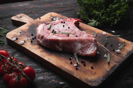 raw steak on the table, fresh meat lies on a cutting board, fragrant spices for meat