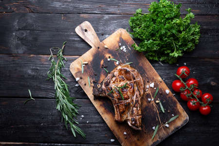 a whole piece of meat on a cutting board, juicy and aromatic steak, grilled, vegetables on the table. Place for text.