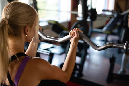 beautiful girl in the gym, active lifestyle, playing sports, trying and struggling with excess weight. Arm exercises