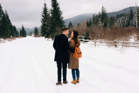 Handsome couple of hipsters look at each other with love. Man and woman walking around winter forest with snowy trees.