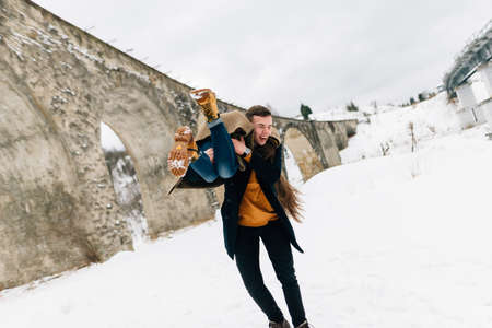 The guy holds and raises his girlfriend in his arms in winter. People have fun in the fresh air between beautiful bridges. Imagens