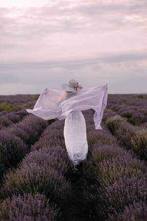 A girl runs on a lavender field in a white dress and a headscarf, France, Provence