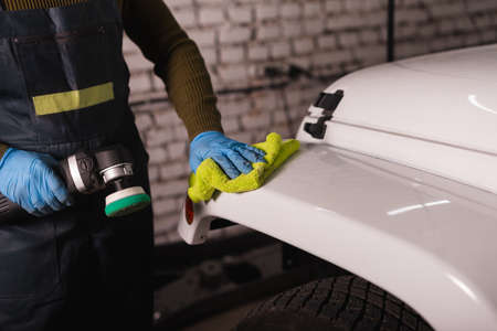 Master in a jumpsuit wipes the cars wing with a yellow rag before polishing
