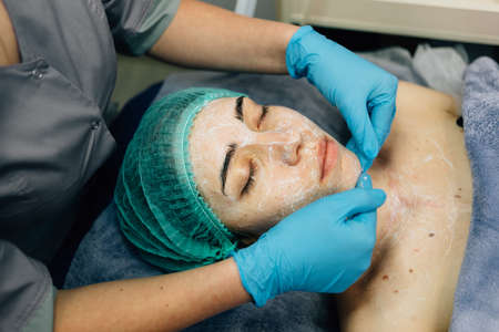 Doctor smasked mask on patients face, professional skin care in beauty salon, close-up.