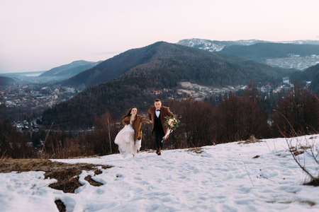 stylish couple of newlyweds running in the snow, men's coat brown, bouquet for the wedding. Holidays for honeymooners at a ski resort. Place for your text. Stock Photo